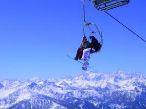 bardonecchia_sciatori sulla seggiovia con panorama delle montagne innevate